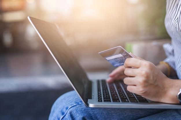 Mulheres jovens, segurando, cartão crédito, e, usando computador portátil