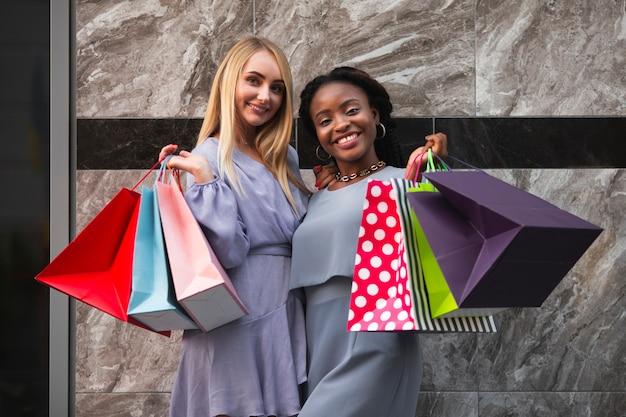 Mulheres jovens segurando sacolas com compras