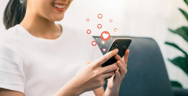 Mulheres jovens segurando smartphones e usando mídias sociais com ícones de coração