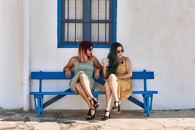 Mulheres jovens sentadas em um banco azul usando óculos escuros