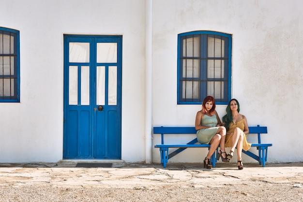Mulheres jovens sentadas em um banco azul