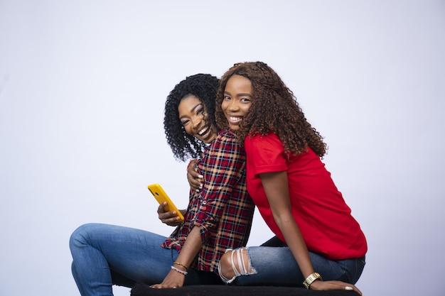 Mulheres jovens sentadas juntas, animadas, abraçadas e um telefone