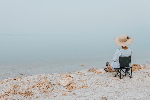 Mulheres jovens sentadas relaxando na cadeira de piquenique na praia olhando o lindo mar