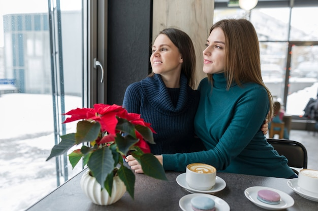 Mulheres jovens, sentado em uma mesa na cafeteria