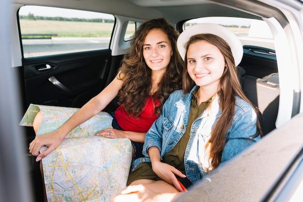 Mulheres jovens, sentando, com, mapa, em, interior carro