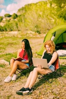 Mulheres jovens, sentando, e, descansar, em, acampamento