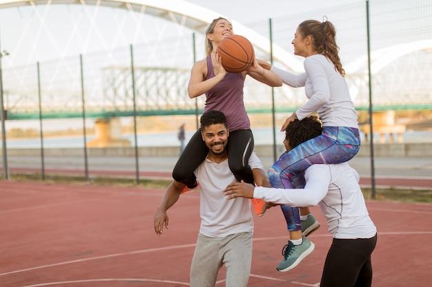 Mulheres jovens, sentando, ligado, a, homens, ombros, e, segurando, um, basquetebol, em, exterior, corte