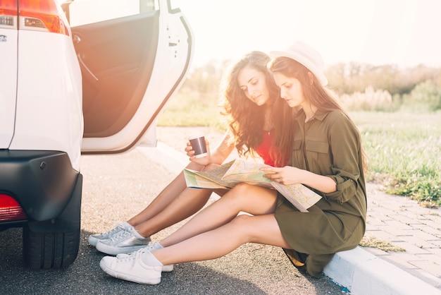 Mulheres jovens, sentando, ligado, borda, com, mapa