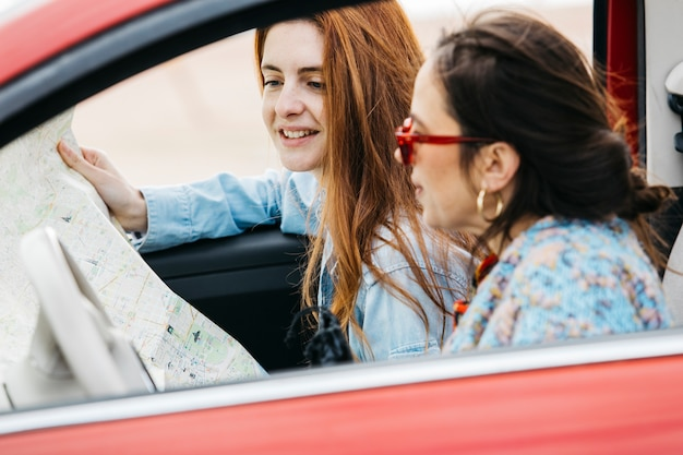 Mulheres jovens, sentar carro, e, olhar, mapa