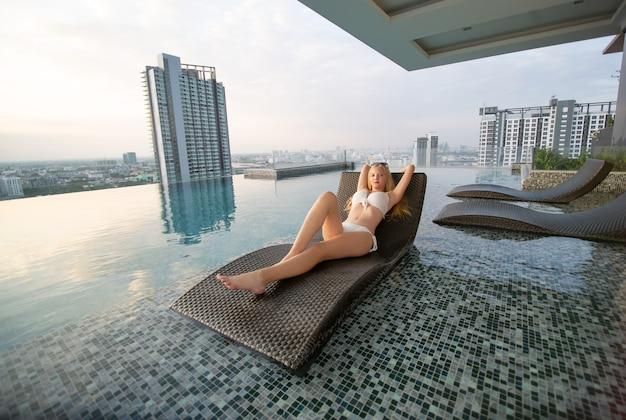 Mulheres jovens sexy em biquíni branco, deitada na cama à beira da piscina.
