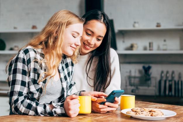 Mulheres jovens, surfando, em, smartphone