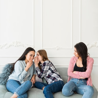 Mulheres jovens, sussurrando, atrás de, amigo
