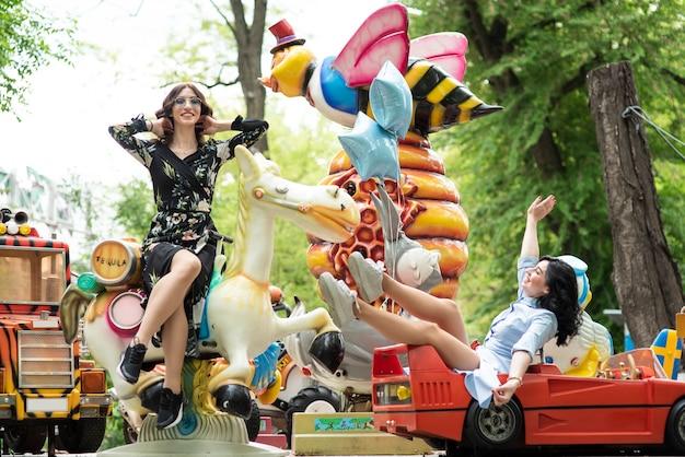 Mulheres jovens, tendo divertimento, em, parque divertimento