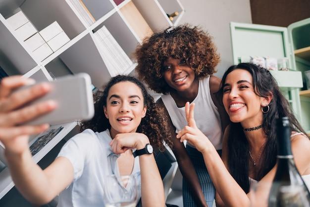 Mulheres jovens, tendo selfie e se divertindo em localização moderna