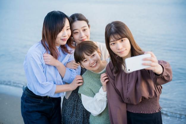 Mulheres jovens tirando uma foto comemorativa com um smartphone