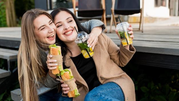 Mulheres jovens tomando sanduíches e coquetéis ao ar livre