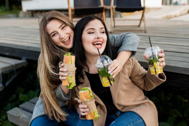 Mulheres jovens tomando sanduíches e coquetéis lá fora
