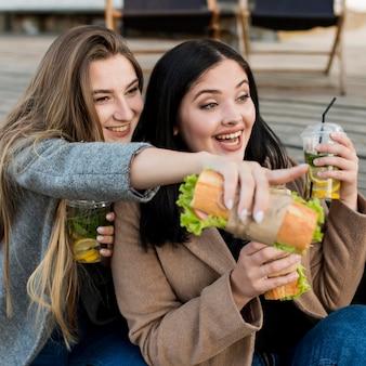 Mulheres jovens tomando sanduíches e coquetéis