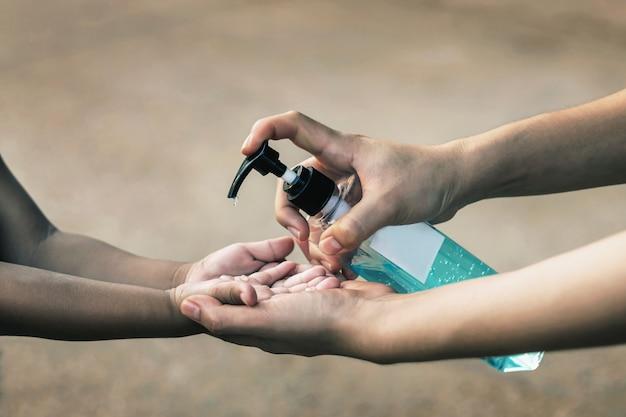Mulheres jovens usam desinfetante para as mãos para matar os germes das crianças.