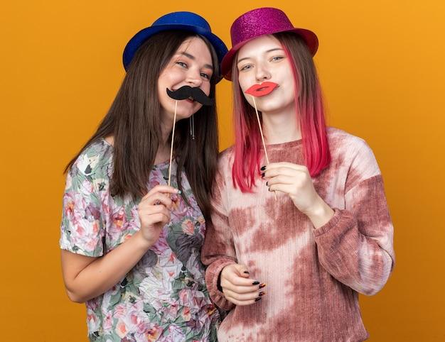 Mulheres jovens usando chapéu de festa segurando um bigode falso em um palito isolado na parede laranja