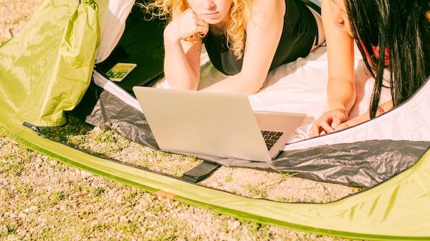 Mulheres jovens, usando computador portátil, em, barraca