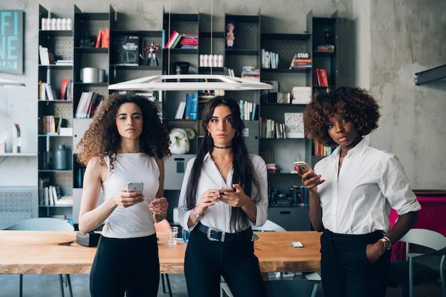 Mulheres jovens, usando, smartphone, e, olhando câmera