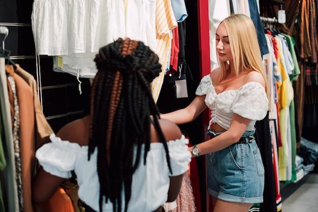 Mulheres jovens, verificando a loja de roupas