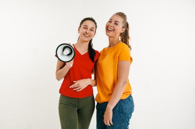 Mulheres jovens vestidas com as cores da bandeira lgbt isoladas na parede branca conceito orgulho lgbt