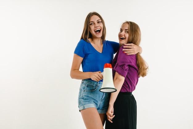 Mulheres jovens vestidas com as cores da bandeira lgbt na parede branca. modelos em camisas brilhantes