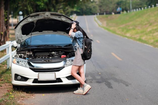 Mulheres jovens viajante asiático com mochila tem carro quebrado e à espera de ajuda