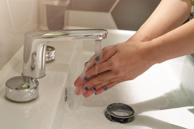 Mulheres lavando as mãos sob a água de fauce. conceito de higiene.