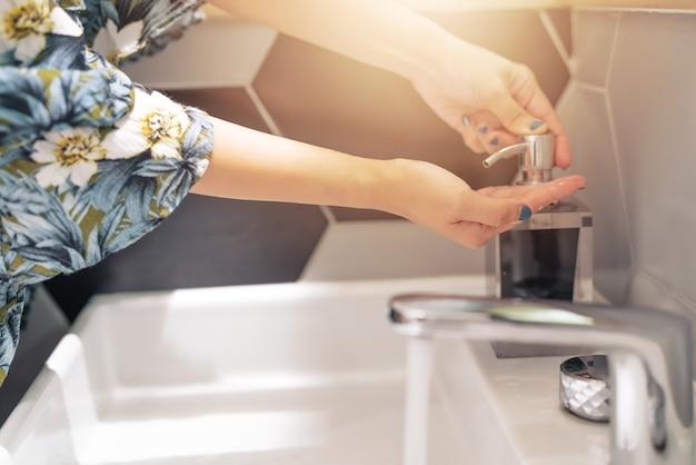 Mulheres, lavando, mão, com, sabonete líquido, em, restroom