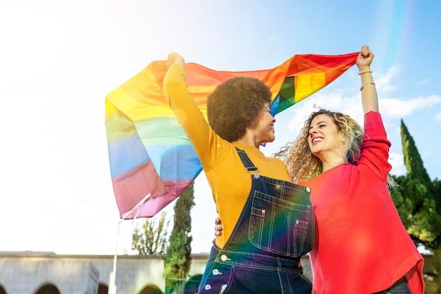 Mulheres lésbicas de diferentes etnias e nacionalidades com bandeira gay