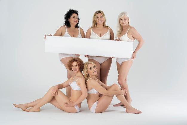 Mulheres lindas de diferentes formas e idades em lingerie com cartaz em branco