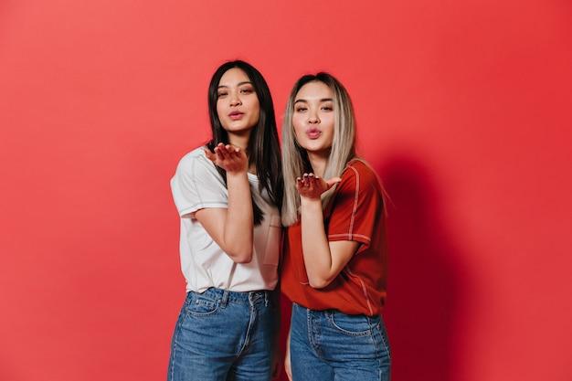 Mulheres lindas em roupas semelhantes mandam beijos contra a parede vermelha