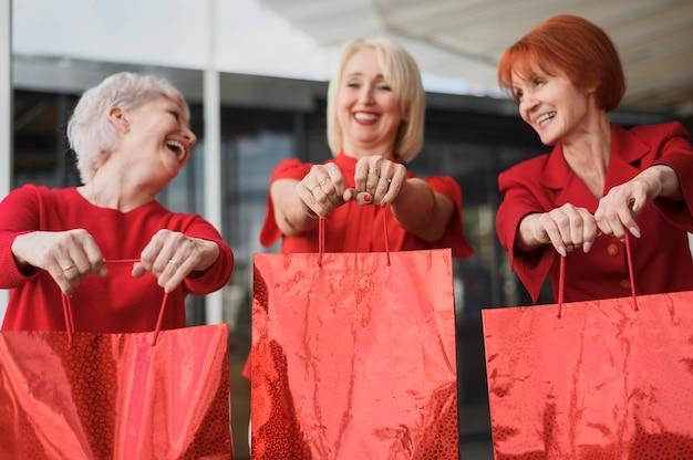 Mulheres maduras com sacos sorrindo