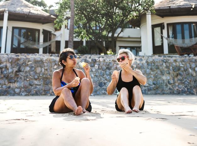 Mulheres maduras de bronzeamento na praia