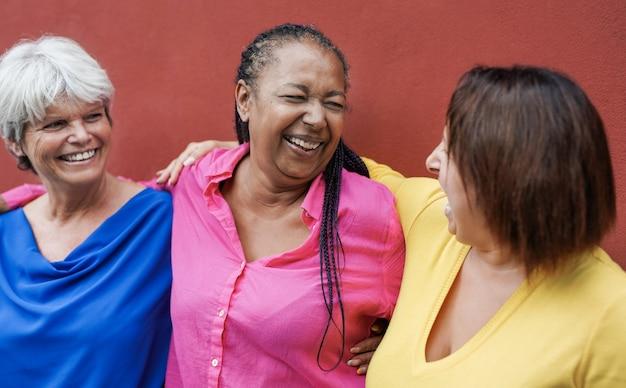 Mulheres maduras multirraciais se abraçando na cidade com uma parede vermelha no fundo - idosos e conceito de amizade