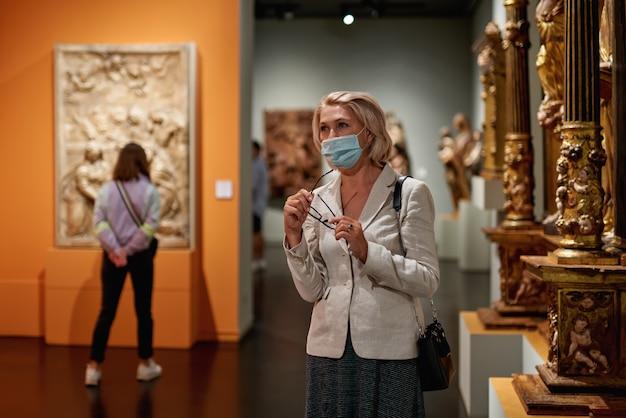 Mulheres maduras observando artes no museu. excursão com grupo