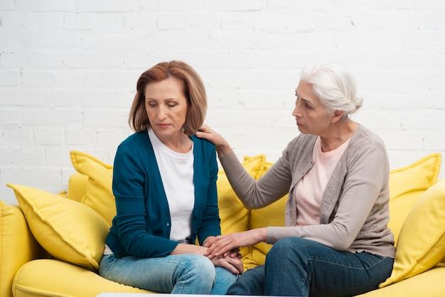 Mulheres maduras, sentado em um sofá Foto gratuita
