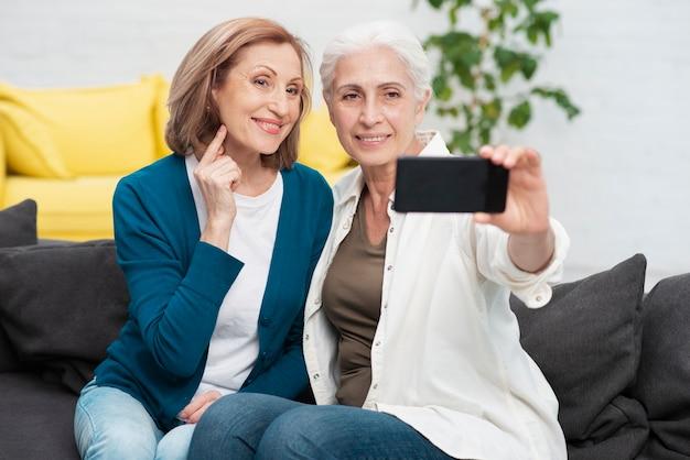 Mulheres maduras, tirando uma foto juntos