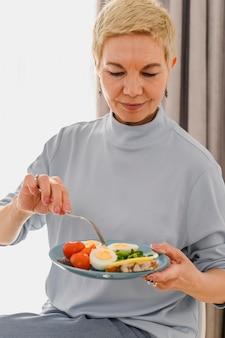 Mulheres maduras tomam café da manhã com alimentos saudáveis em um prato, bio vegetais frescos e ovos saudáveis Foto Premium