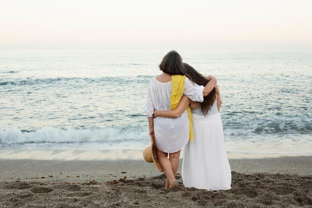 Mulheres mais velhas admirando o oceano juntas enquanto se abraçavam na praia