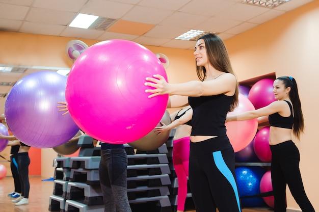 Mulheres malhando com bola de exercício no ginásio