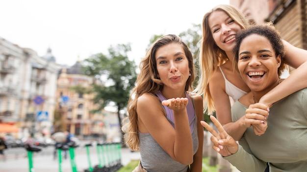 Mulheres mandando beijos e mostrando o símbolo da paz