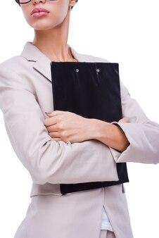 Mulheres mandonas. imagem recortada de uma jovem empresária confiante segurando a prancheta enquanto fica de pé contra um fundo branco