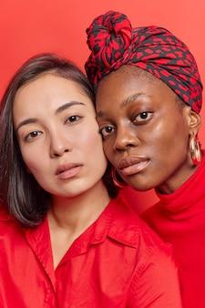 Mulheres mantenham o rosto de perto, olhem seriamente para a câmera, tenham uma pele saudável e macia isolada no vermelho