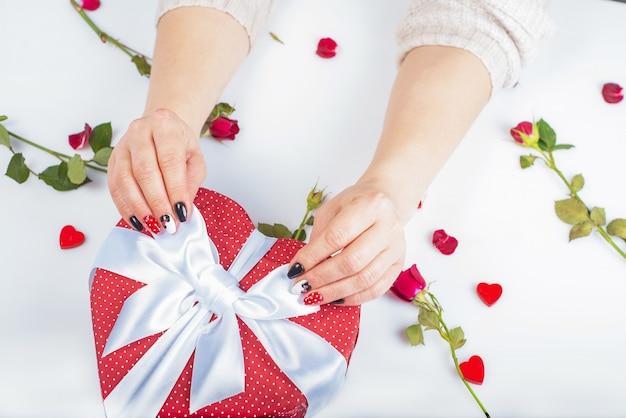 Mulheres mão com linda bem cuidada segurando caixa de presente em forma de coração.