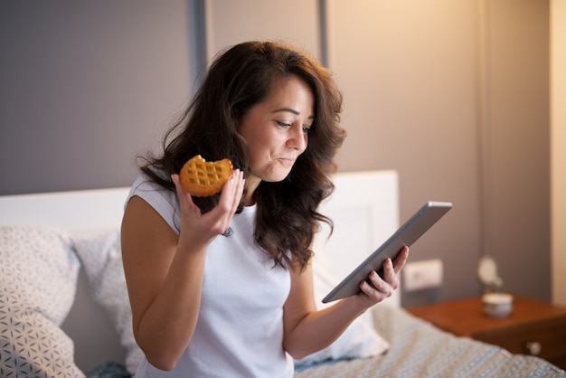Mulheres meio envelhecidas consideravelmente satisfeitas que sentam-se na cama e que olham em uma tabela antes de dormir ao comer um biscoito.