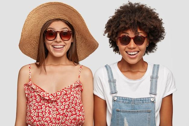 Mulheres mestiças alegres viajam juntas, andando lado a lado, sorrindo positivamente